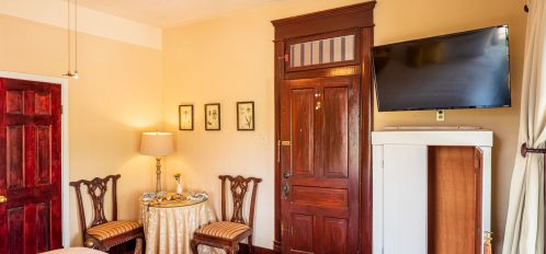 Magpie Inn - Room 2 - Wardrobe with TV mounted above and small seating area