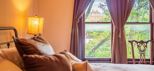 Magpie Inn - Room 4 - Close up of bedside and large windows on far wall