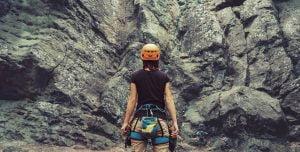 woman facing rock tower with rock climbing gear